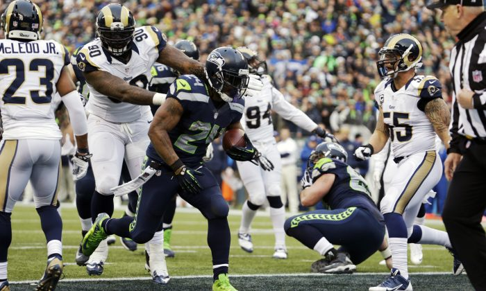 Seattle Seahawks running back Marshawn Lynch runs for a touchdown ahead of St. Louis Rams defensive tackle Michael Brockers (90) in the second half of an NFL football game, Sunday, Dec. 29, 2013, in Seattle. (AP Photo/Elaine Thompson)