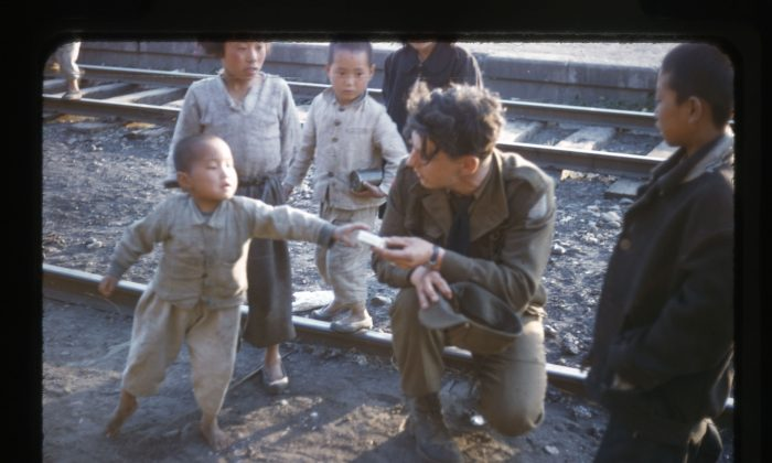 A Canadian gunner hands candy to a Korean boy at the rail yards in Tokchon, South Korea. (George Metcalf Archival Collection, © Canadian War Museum)