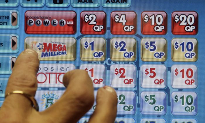 A clerk prepares to operate a lottery machine to print out Mega Millions lottery tickets for a customer at Tobacco Plus, Tuesday, Dec. 17, 2013, in Muncie, Ind. With tickets selling well, the jackpot for tonight's drawing is now at an estimated $636 million, the second-biggest lottery prize in U.S. history. (AP Photo/Darron Cummings)