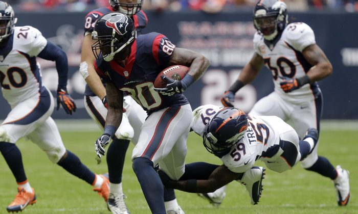 Houston Texans' Andre Johnson (80) tries to evade the tackle of Denver Broncos' Danny Trevathan (59) after he made a catch during the second quarter of an NFL football game on Sunday, Dec. 22, 2013, in Houston. (AP Photo/Patric Schneider)