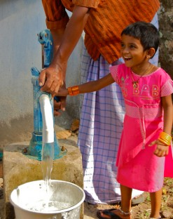 July, 2013 - Achinakom, India - A child helps retrieve water from a rainwater tank designed by Rainwater for Humanity. (Annie Sholar/R4H)