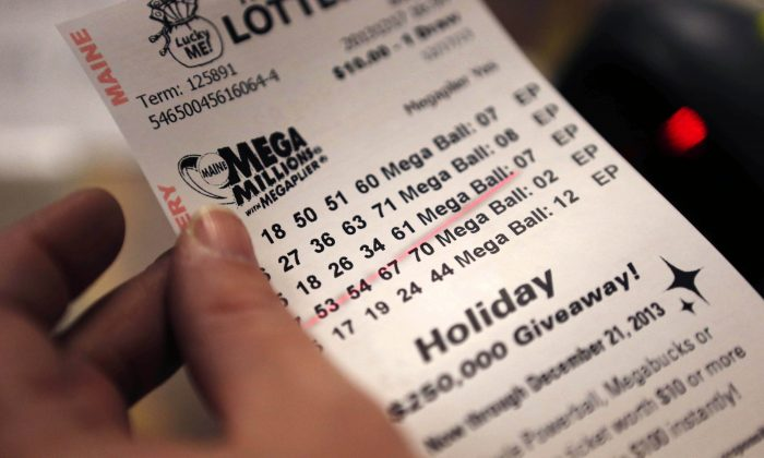 A cashier holds a Mega Millions lottery ticket at a convenience store in Lisbon, Maine, Tuesday, Dec. 17, 2013. (AP Photo/Robert F. Bukaty)