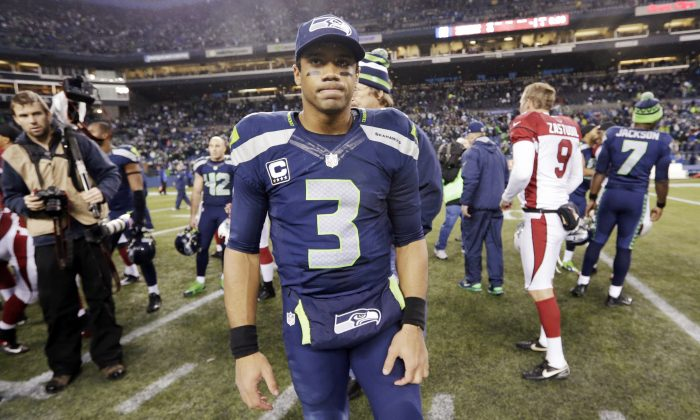 Seattle Seahawks quarterback Russell Wilson (3) waits to greet Arizona Cardinals players after an NFL football game, Sunday, Dec. 22, 2013, in Seattle. The Cardinals won 17-10. (AP Photo/Elaine Thompson)