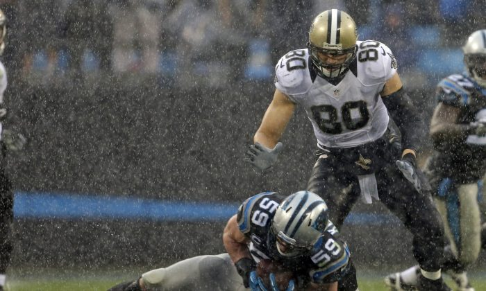 In the rain, Carolina Panthers' Luke Kuechly (59) intercepts a pass intended for New Orleans Saints' Jimmy Graham (80) in the second half of an NFL football game in Charlotte, N.C., Sunday, Dec. 22, 2013. (AP Photo/Bob Leverone)