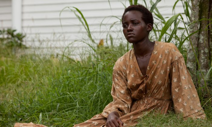 "This image released by Fox Searchlight shows Lupita Nyong'o in a scene from ""12 Years A Slave."" Nyong'o was nominated for a Golden Globe for best supporting actress in a motion picture for her role in the film on Thursday, Dec. 12, 2013.  The 71st annual Golden Globes will air on Sunday, Jan. 12. (AP Photo/Fox Searchlight, Francois Duhamel)"