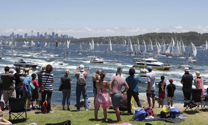 Spectators watch as the fleet sail out of the heads at the start of the Sydney Hobart yacht race in Sydney Thursday, Dec. 26, 2013. (AP Photo/Glenn Nicholls)