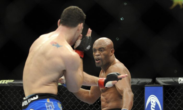 Anderson Silva, right, of Brazil, prepares to kick Chris Weidman of Baldwin, N.Y., during the UFC 168 mixed martial arts middleweight championship bout on Saturday, Dec. 28, 2013, in Las Vegas. Weidman won during the second round by a technical knock out after Silva was injured. (AP Photo/David Becker)