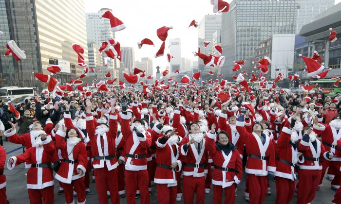 More than 1,000 volunteers clad in Santa Claus costumes throw their hats in the air as they gather to deliver gifts for the poor in downtown Seoul, South Korea, Tuesday, Dec. 24, 2013. (AP Photo/Lee Jin-man)
