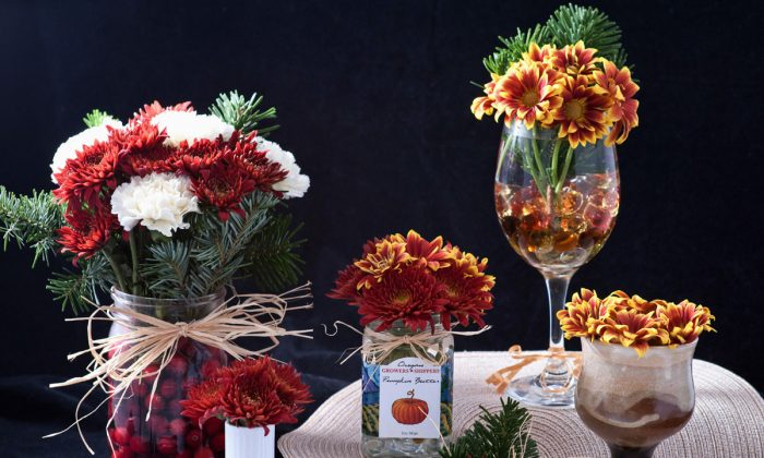 Holiday flower arrangements using one flower bouquet, fresh cranberries, and various mini-vases. (Cat Rooney/Epoch Times)