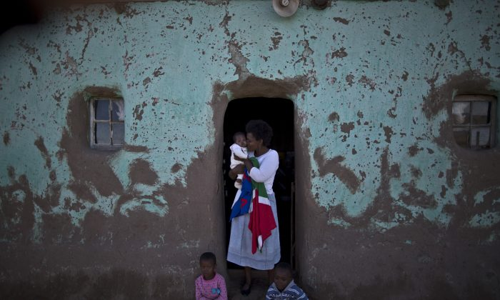 A South African woman holds her child at the doorway of her home during the funeral service of former President Nelson Mandela, in Qunu, South Africa, Sunday, Dec. 15, 2013. (AP Photo/Muhammed Muheisen)