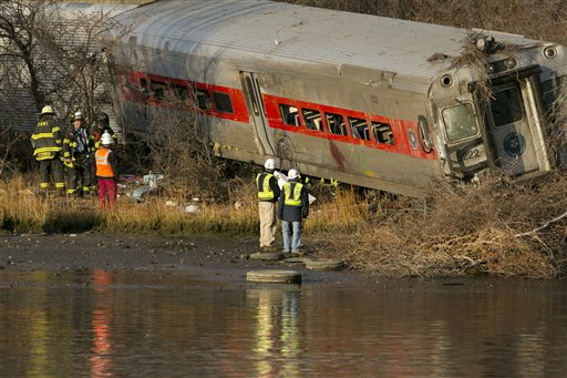 Officials with the National Transportation Safety Board inspect a derailed Metro North commuter train where it almost fell into the Harlem River, Sunday, Dec. 1, 2013 in the Bronx borough of New York. The Metro-North train derailed on a curved section of track early Sunday, coming to rest just inches from the water, killing at least four people and injuring more than 60, authorities said. (AP Photo/Mark Lennihan)