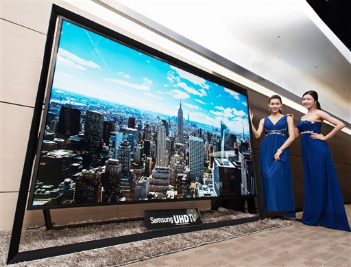 In this undated handout photo released by Samsung Electronics Co. Monday, Dec. 30, 2103, models pose with a Samsung Electronics' 110-inch UHD TV. (AP Photo/Samsung Electronics Co.)