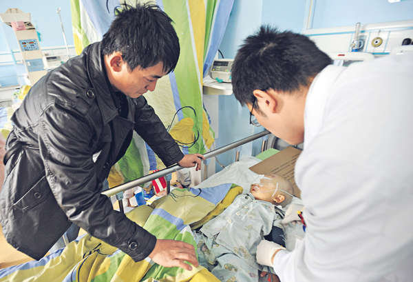 Screenshot showing Yuanyuan's father (left) and a doctor (right) caring for him in hospital, after he was attacked by a 10-year-old girl. (Sky Post/Screenshot/Epoch Times)
