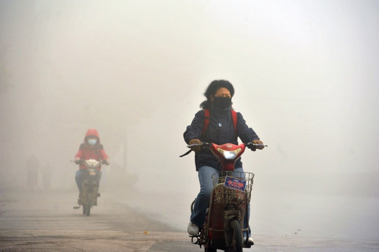 Screenshot shows residents riding motorcycles with masks on faces on smoggy day in southern China's Nanjing City on Dec. 7. (Netease/screenshot/Epoch Times)