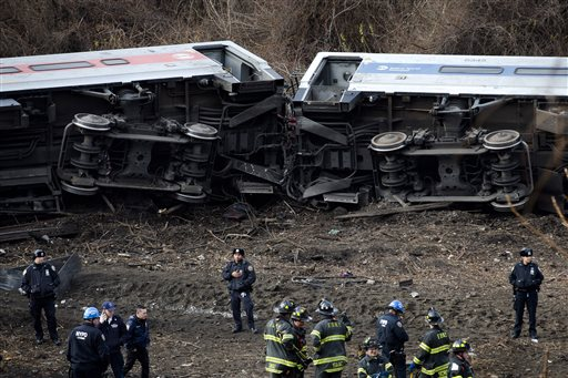 Emergency personnel respond to the scene of a Metro-North passenger train derailment in the Bronx borough of New York, Dec. 1, 2013. A preliminary report by federal investigators on last year's deadly train derailment in in the Bronx does not draw any conclusions about what caused the wreck. (AP Photo/John Minchillo)