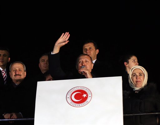 In this photo taken late Tuesday, Dec. 24, 2013, Turkey's Prime Minister Recep Tayyip Erdogan, center, is flanked by his wife Emine Erdogan, right, and Economy Minister Zafer Caglayan, left, as he addresses supporers at the Esenboga Airport, Ankara, Turkey. Interior Minister Muammer Guler and Caglayan resigned from their posts on Wednesday, Dec. 25, 2013, days after their sons were arrested in a massive corruption and bribery scandal that has targeted Prime Minister Recep Tayyip Erdogan's allies and has become the worst crisis in his decade in power. Caglayan and Guler both stepped down on Wednesday, despite denying any wrongdoing.(AP Photo)