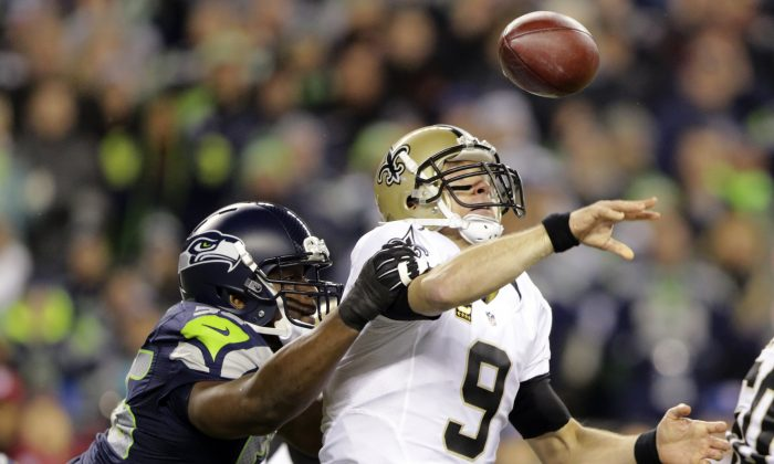 In this Dec. 2, 2013, file photo, Seattle Seahawks defensive end Cliff Avril hits the arm of New Orleans Saints quarterback Drew Brees causing a fumble that was returned for a touchdown by Seahawks defensive end Michael Bennett in the first half of an NFL football game in Seattle. The Seahawks finished the regular season as the best pass defense in the NFL with three All-Pro selections in the secondary. Their best performance came when they suffocated New Orleans in Week 13. Now comes the challenge of duplicating that in Saturday's NFC divisional playoff game against the Saints. (AP Photo/Scott Eklund, File)