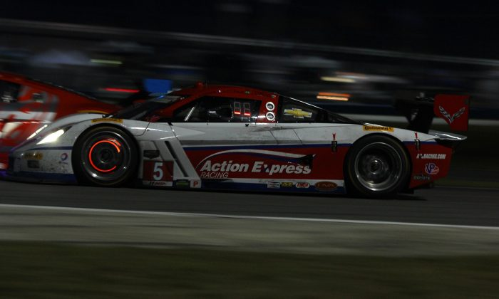 Joao Barbosa drives the #5 Action Express Coyote-Corvette deep into Daytona's International Horseshoe, brake discs glowing with heat, as he pushes on in the lead of the TUSC Rolex 24. (Chris Jasurek/Epoch Times)