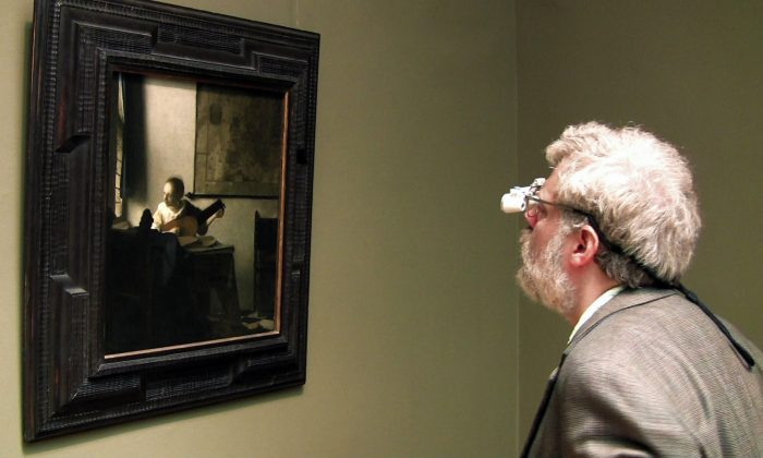 """Tim Jenison, wearing his surgical loupes, inspects Johannes Vermeer's """"Woman with a Lute"""" at the Metropolitan Museum of Art in New York. (Shane F. Kelly, High Delft Pictures LLC, Courtesy of Sony Pictures Classics)"""