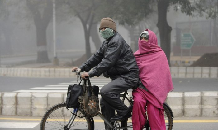 An Indian couple travel on a bicycle through dense fog in New Delhi; the city is currently experiencing winter chill. The new government has decided to convert abandoned buses into winter shelters for homeless people.(Raveendran/AFP/Getty Images)