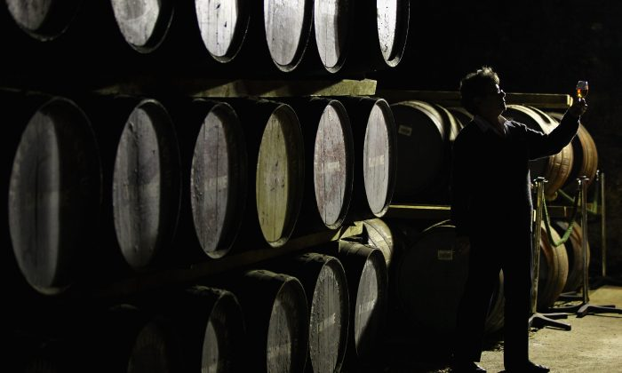 Maureen Stronach, an employee at Diageo's Dalwhinnie distillery views whisky drawn from a cask the store room in Dalwhinnie, Scotland.(Photo by Jeff J Mitchell/Getty Images)