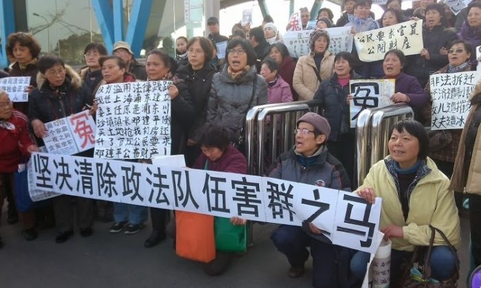 """Petitioners hold banners at the Shanghai Expo Center, site of the annual political """"Two Sessions."""" One banner reads, """"Clear Away the Black Horse in Political and Legislative Affairs Committee!"""" Jan. 19, 2014. (Provided by a petitioner)"""