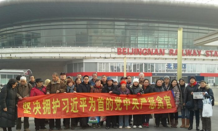 """Petitioners who have come to Beijing to seek redress of grievances raise a banner that reads, """"We firmly support the Party Central Committee, headed by Xi Jinping, in punishing corrupt officials"""" in front of the Beijing South Railway Station on Jan. 24, 2014.(Human Rights Campaign in China)"""