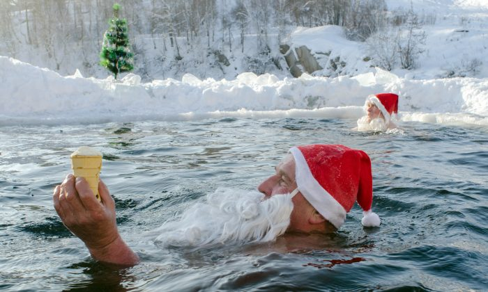 A Russian man holds an ice cream as he swims with other people dressed as Santa Claus in an ice-hole of a pond in the Siberian city of Novosibirsk, on the eve of the New Year's 2013 celebrations. (VALERY TITIEVSKY/AFP/Getty Images)