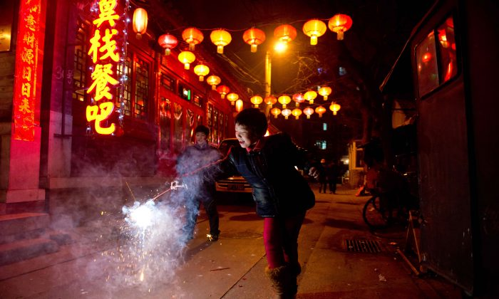 A girl holds a firecracker in an alleyway in Beijing during the Lantern Festival, which marks the end of celebrations for the Chinese New Year period. (Ed Jones/AFP/Getty Images)
