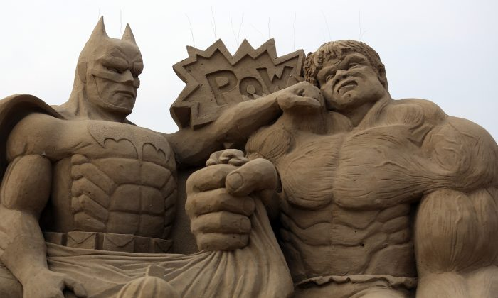 D.C. and Marvel comic superheroes cross over in this sand sculpture of Batman and the Incredible Hulk in an early 2013 sand sculpure festival in England. There may be more going on in the greater subconscious, however, than just a surface-level pop culture phenomenon. (Matt Cardy/Getty Images)