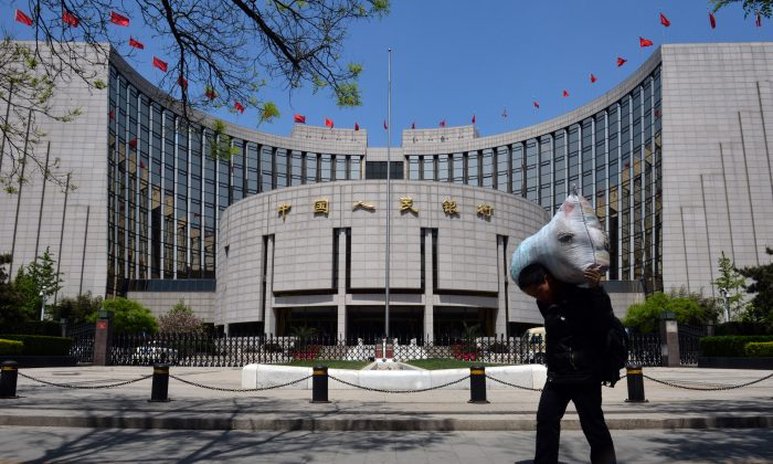 In this file photo, a Chinese migrant worker passes by The People's Bank of China in Beijing on May 1, 2013. China's banking system is curently suffering from a cash shortage. (MARK RALSTON/AFP/Getty Images)