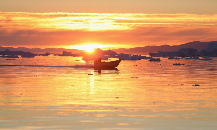 A boat cruises past icebergs that broke off from the Jakobshavn Glacier as the sun reaches its lowest point of the day on July 23, 2013 in Ilulissat, Greenland. (Joe Raedle/Getty Images)