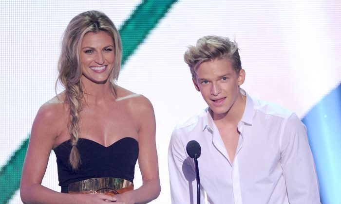 TV personality Erin Andrews (L) and singer Cody Simpson speak onstage during the Teen Choice Awards 2013 at Gibson Amphitheatre on August 11, 2013 in Universal City, California. (Photo by Kevin Winter/Getty Images)