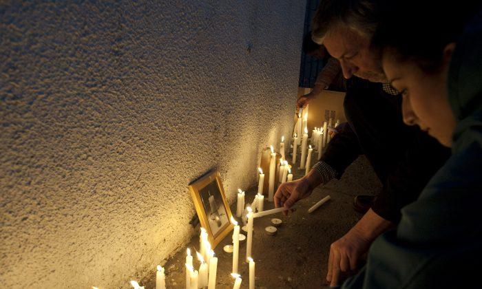 People light candles at the gates of the National Stadium, on September 11, 2013 in Santiago, Chile, during the commemoration of the 40th anniversary of the military coup led by General Augusto Pinochet that deposed President Salvador Allende. (Claudio Santana/AFP/Getty Images)