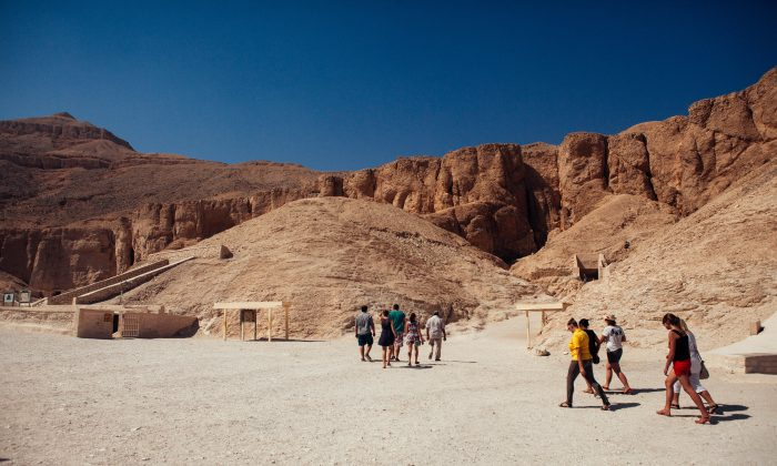 A small group of tourists walk toward the entrance to a tomb in The Valley of the Kings on October 23, 2013 in Luxor, Egypt. (Ed Giles/Getty Images)