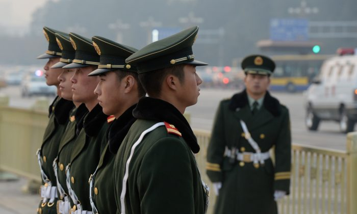 In this file photo, Chinese para-military police stand guard in Tiananmen Square in Beijing on Nov. 8, 2013. High-ranking security officials associated with the persecution of Falun Gong have recently been arrested. (Mark Ralston/AFP/Getty Images)