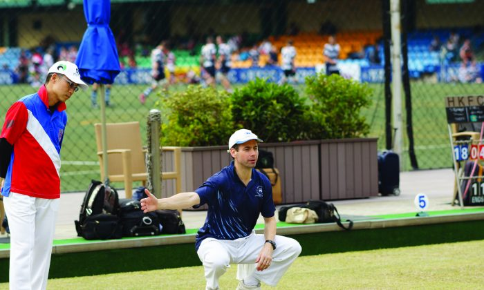 Hong Kong Football Club's Neil Herrington (in blue) directs play during his Triples League match against Stanley Lai of Kowloon Bowling Green Club on Saturday Jan 25, 2014. Herrington lost 9:26. KBGC won the game 6-2 and moved within one point from the leader Kowloon Cricket Club. (Mike Worth)