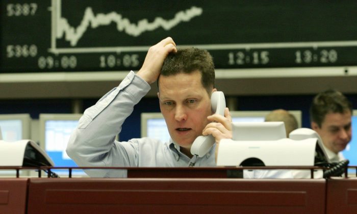 A trader sitting in front of a stock chart at a stock exchange gestures as he speaks on the phone in this file photo. Look on weakness in a stock as cause for concern and further investigation. But don't sell just because a stock went down. (Thomas Lohnes/AFP/Getty Images)