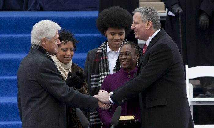 Former President Bill Clinton (L) shakes hands with New York Mayor Bill de Blasio (R) as his daughter, Chiara, son, Dante, and wife, Chirlane McCray, look on, at the inauguration ceremony at New York City Hall on Jan. 1, 2014. (Samira Bouaou/Epoch Times)