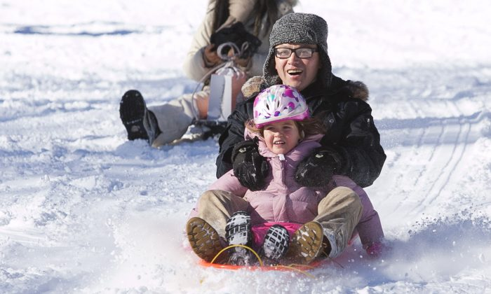 People enjoy sledding and tobogganing south of the Metropolitan Museum in Central Park in New York on Jan 3, 2014. (Samira Bouaou/Epoch Times)