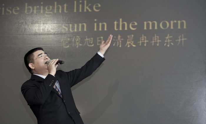 Chen Guangbiao sings karaoke at a press conference he called for the morning of Jan. 7, 2014, in a hotel in New York City. Lyrics to the song he is singing, in Chinese and English, were projected onto the wall behind him. (Samira Bouaou/Epoch Times)