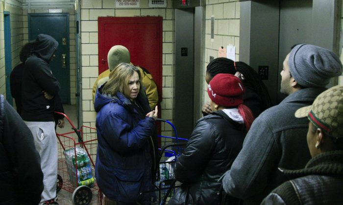 Residents of Wagner Houses in East Harlem wait for the elevator with flats of water after losing water service, New York, Jan. 7, 2014. (Genevieve Belmaker/Epoch Times)
