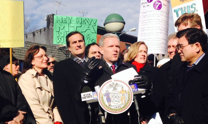 Council member Jimmy Van Bramer (C), N.Y. state Sen. Michael Gianaris (2nd L), Queens Borough President Melinda Katz (3rd L), other officials, small-business owners, and community members protest subway No. 7 line service suspensions in front of the Vernon Boulevard-Jackson Avenue Station, Queens, New York, Jan. 17, 2014. (Yi Yang).