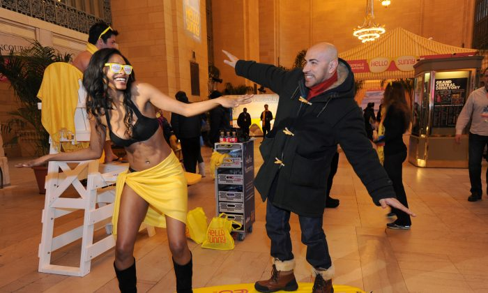 Sisco Muniz surfs with a model at the Hello Sunny Beach promotion at Grand Central Terminal in New York, Jan. 28, 2014. (Diane Bondareff/Invision for Greater Fort Lauderdale/AP)
