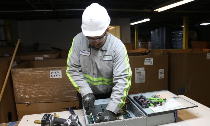 A Hugo Neu Recycling employee removes a circuit board from an old computer at the Hugo Neu warehouse in Mount Vernon, N.Y., Jan. 28, 2014. (Allen Xie)