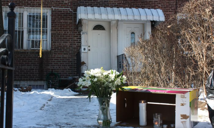 Flowers and candles in front of 24-10 87th St., in East Elmhurst, Queens, New York, on Jan. 29, 2014, where Estrella Castaneda and her daughter Lina Castaneda were found dead around midnight on Jan. 28. Carlos Amarillo has been charged with their murders. (Jane Gray/Epoch Times)