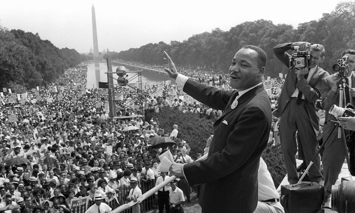 "US civil rights leader Martin Luther King, Jr., waves to supporters from the steps of the Lincoln Memorial 28 August, 1963, on The Mall in Washington, DC, during the ""March on Washington"" where King delivered his famous ""I Have a Dream"" speech, which is credited with mobilizing supporters of desegregation and prompted the 1964 Civil Rights Act. (AFP/Getty Images)"