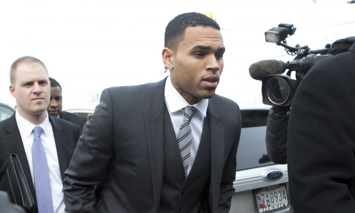 FILE - This Jan. 8, 2014 file photo shows singer Chris Brown, right, arriving at the District of Columbia Superior Court in Washington. District of Columbia police officials are investigating whether a police officer made contradictory statements in the assault case against Brown. The department's internal affairs investigation stems from a disputed conversation between the officer and an unidentified acquaintance of Brown. The discrepancies in the exchange, which could become important as the criminal prosecution moves forward, are summarized in police documents that lay out the basis for charging Brown and his bodyguard with punching a man outside a Washington hotel in October.   (AP Photo/Manuel Balce Ceneta, File)