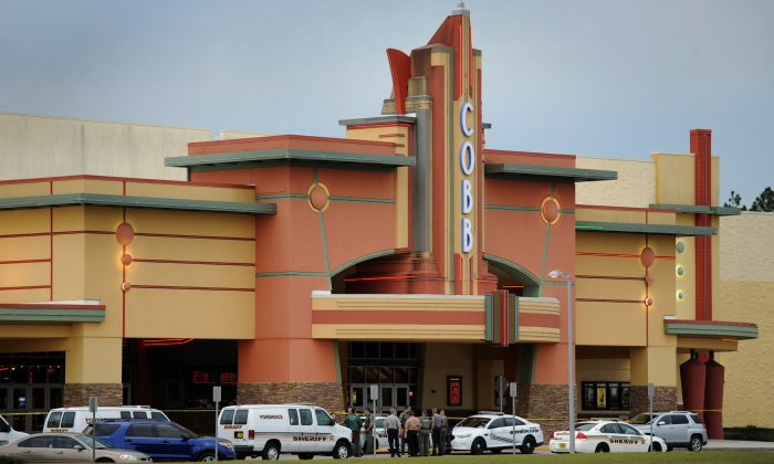 Authorities stand outside Cobb theater after a shooting in Wesley Chapel, Fla., Monday, Jan. 13, 2014. Authorities say a retired Tampa police officer has been charged with fatally shooting a man during an argument over cellphone use at the theater. (AP Photo/The Tampa Tribune, Cliff Mcbride)