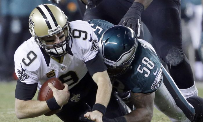 Philadelphia Eagles' Trent Cole (58) tackles New Orleans Saints' Drew Brees (9) during the first half of an NFL wild-card playoff football game, Saturday, Jan. 4, 2014, in Philadelphia. (AP Photo/Matt Rourke)